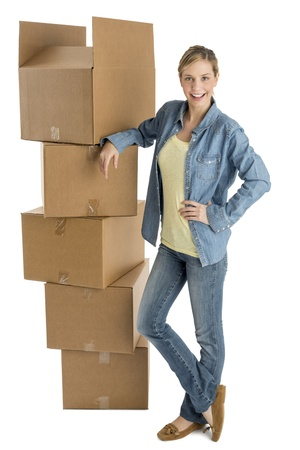 Full length portrait of beautiful young woman with hand on hip standing by stacked cardboard boxes isolated over white background photo