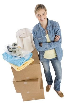 Full length portrait of confident young woman standing by stacked cardboard boxes with towels; adhesive tape and lamp shade on it over white background photo