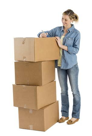Full length of happy young woman writing on stacked cardboard boxes against white background