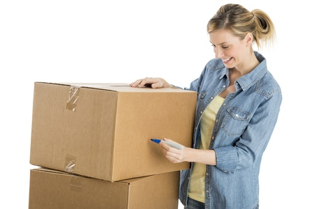 Happy young woman writing on cardboard boxes isolated over white background photo