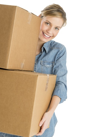 Portrait of beautiful young woman carrying stacked cardboard boxes against white background photo