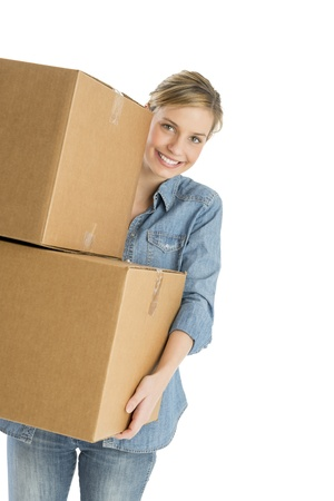 Portrait of happy young woman carrying stacked cardboard boxes isolated over white background photo