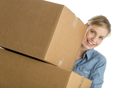 only young adults: Portrait of happy young woman carrying stacked cardboard boxes against white background