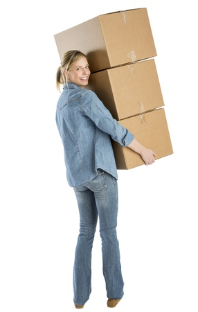 Full length portrait of happy young woman carrying stacked cardboard boxes against white background photo