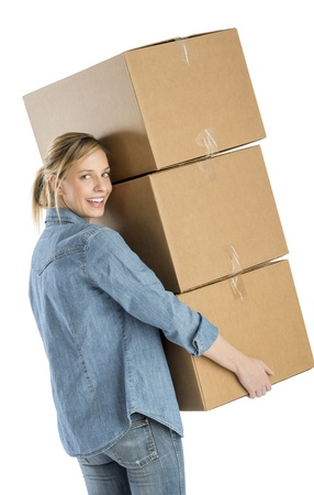 Rear view portrait of happy young woman carrying stacked cardboard boxes isolated over white background photo