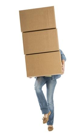 boite carton: Section basse de la jeune femme transportant des bo�tes de carton empil�es en position debout sur une jambe sur fond blanc Banque d'images