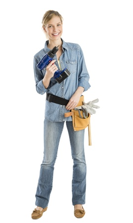 Full length portrait of happy female construction worker with drill and tool belt standing isolated over white background photo