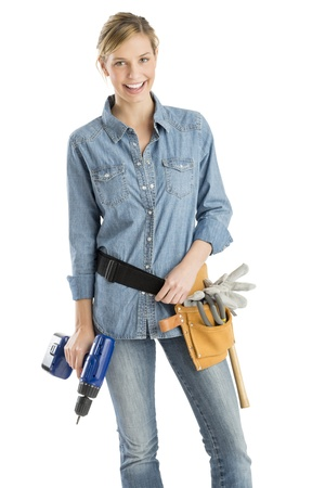 female construction worker: Portrait of beautiful female construction worker with drill and tool belt standing isolated over white background