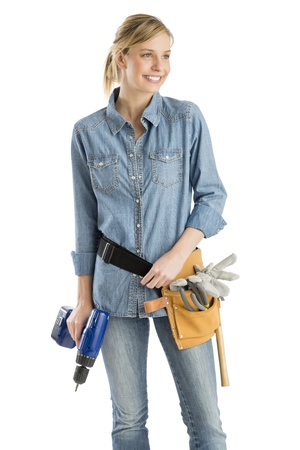 Young female construction worker with tool belt and drill looking away against white background photo