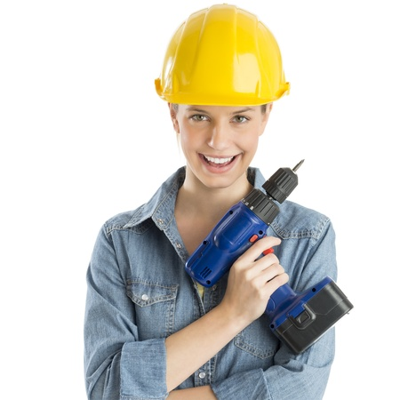 Portrait of confident female construction worker wearing helmet while holding drill against white background