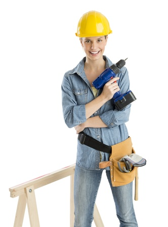 female construction worker: Portrait of confident female construction worker with drill and tool belt standing by work horse against white background