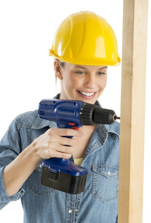 Happy female construction worker using cordless drill on wooden plank against white background Banque d'images