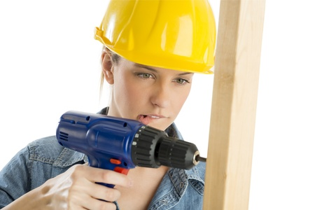 driller: Close-up of beautiful construction worker biting lip while drilling wooden plank isolated over white background
