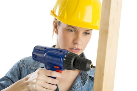 female construction worker: Close-up of young female construction worker using cordless drill on wooden plank against white background