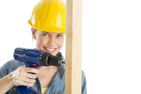 Portrait of happy female construction worker drilling wooden plank against white background photo