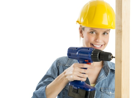 Portrait of beautiful construction worker using power drill on wooden plank isolated over white background