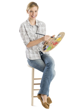 creative artist: Full length portrait of happy female artist with palette and paintbrush sitting on stool against white background Stock Photo