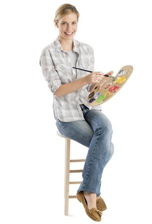 Full length portrait of happy female artist with palette and paintbrush sitting on stool against white background Standard-Bild