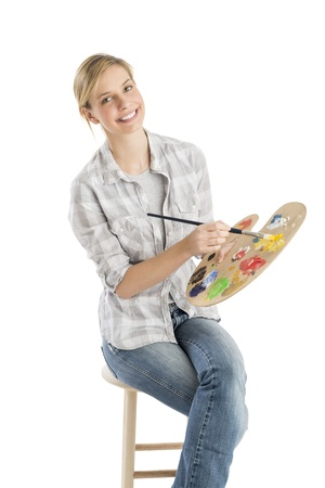 Portrait of happy female artist holding palette and paintbrush sitting on stool against white background photo