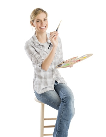 Portrait of happy female artist with paintbrush and palette sitting on stool against white background Reklamní fotografie