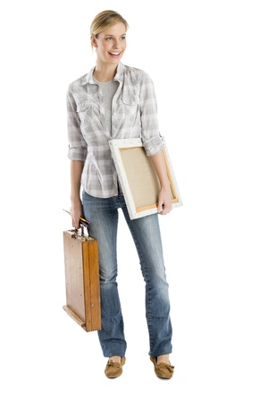 20 s: Full length of young woman carrying canvas and wooden case while looking away against white background Stock Photo