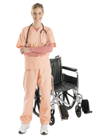 Full length portrait of confident female nurse smiling while standing by wheelchair against white background