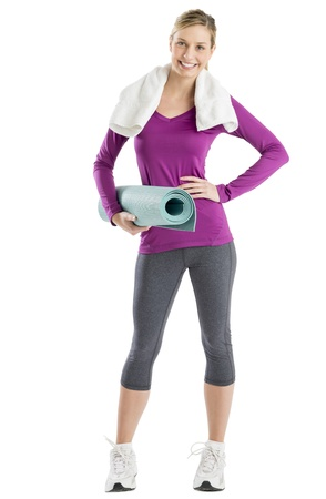 Full length portrait of happy young woman with hand on hip while holding exercise mat against white background photo