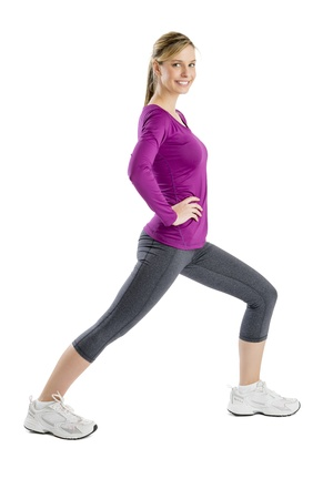 Side view portrait of happy young woman smiling while doing stretching exercise isolated over white background photo