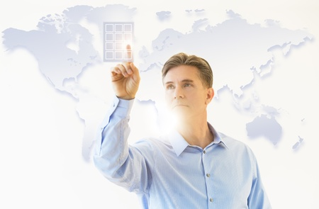 Front view of mature businessman touching virtual keypad with world map in background
