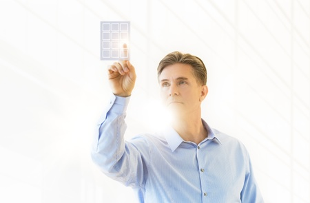 human finger: Front view of mature businessman touching virtual keypad against white background Stock Photo