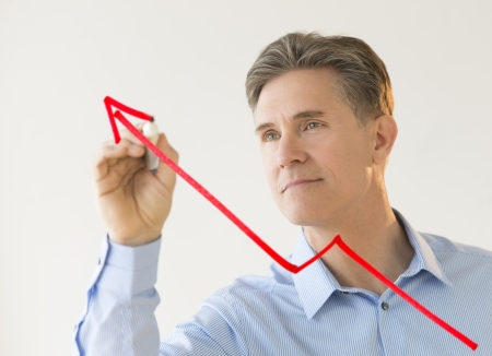 person writing: Mature businessman drawing arrow moving upwards on transparent board against white wall