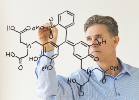 virtual reality simulator: Mature male scientist drawing molecular structure on transparent board against white wall Stock Photo