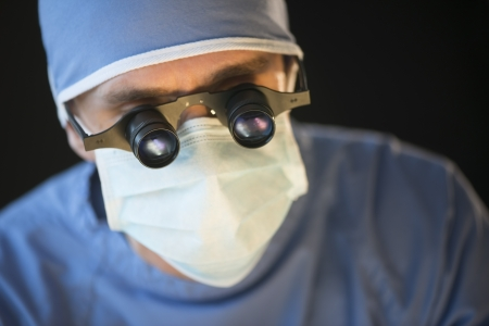 Close-up of male surgeon wearing mask and magnifying glasses against black background