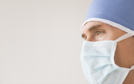 Close-up of male surgeon wearing surgical mask and cap looking away against gray background photo