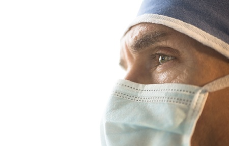 Side view of male surgeon wearing surgical mask and cap looking away against white background photo