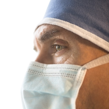 Close-up of male surgeon wearing surgical mask and cap against white background photo