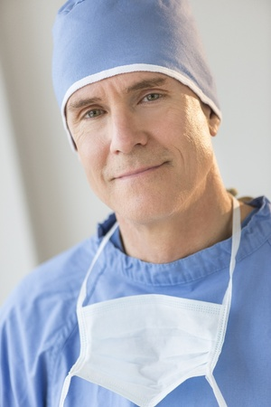 Portrait of confident male surgeon with surgical mask and cap in hospital photo