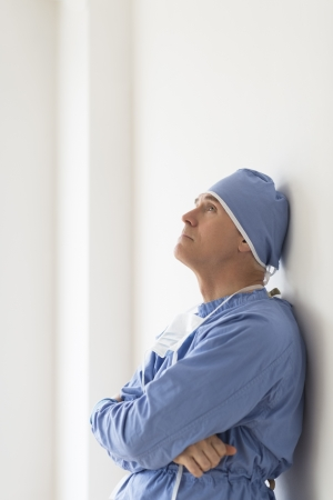 Side view of thoughtful male surgeon with arms crossed leaning on wall in hospital photo