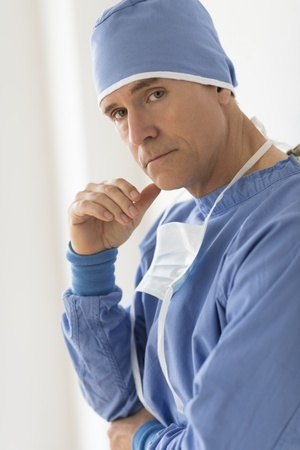 tensed: Portrait of tensed mature male surgeon standing in hospital