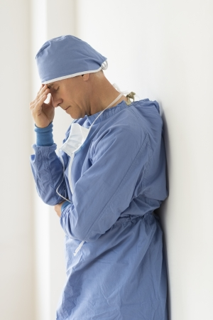 Side view of tensed male surgeon with head in hands standing in hospital photo