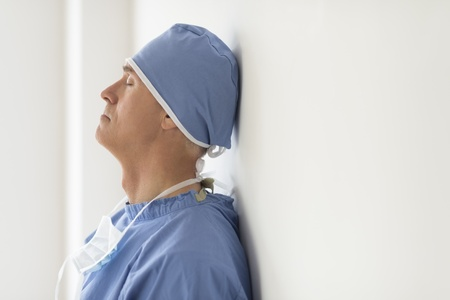 Side view of mature male surgeon with eyes closed leaning on wall in hospital photo