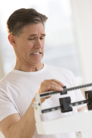 weight scale: Mature man clenching teeth while using balance weight scale at health club