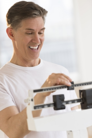 health club: Happy mature man adjusting balance weight scale at health club