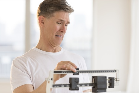 sliding scale: Worried mature man using balance weight scale at gym