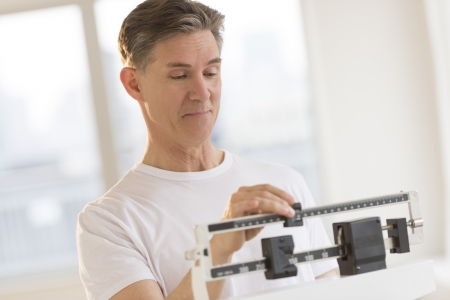 Mature man weighing himself on balance weight scale at health club