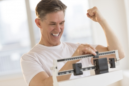 Excited mature man clenching fist while using balance weight scale at gym Standard-Bild