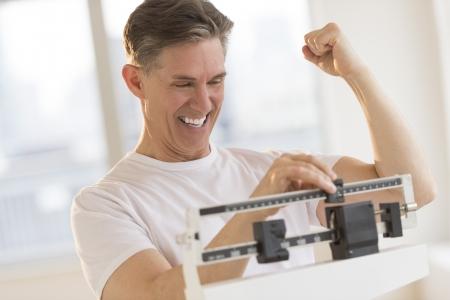 Hombre maduro emocionado apretando el puño, mientras que utilizando la escala de peso de equilibrio en el gimnasio Foto de archivo - 22082340