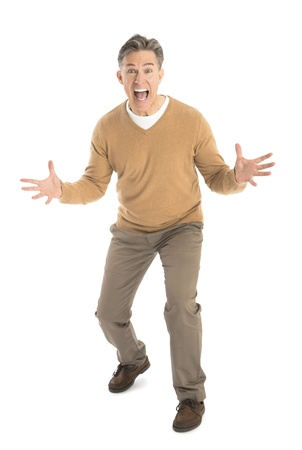 Full length portrait of frustrated mature man screaming while standing isolated on white background Imagens