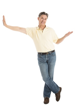 Full length portrait of happy mature man in casuals gesturing while leaning over white background