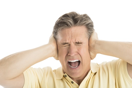 covering: Close-up of furious mature man screaming while covering his ears against white background